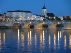 Loire River at twilight with lights twinkling and a bridge and church in the background