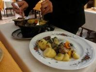 waiter serving baeckeoffe in a restaurant, travel, travel tips, travel planning