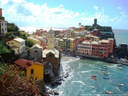 harbour of Vernazza with buildings and blue seas, waves