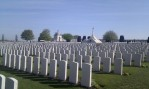 rows of white grave stones on a grassy field