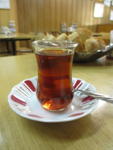 saucer with glass of Turkish tea, dark liquid