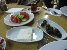 white plates with tomatoes, cucumber, plate of white cheese, plate of marinated olives