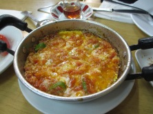 metal bowl filled with egg mixture, green peppers, tomato