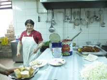 kitchen with utensils on wall, steel kitchen bench, woman in white apron, and pile of chopped onion