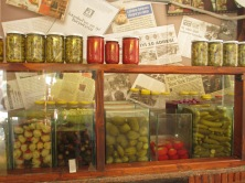 shop display with bottles of vegetables, plastic containers of vegetables in liquid