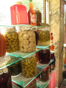 window display, bottles of vegetables in liquid, on display shelves