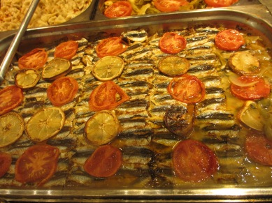 rows of small fish, layered with slices of lemon and tomato
