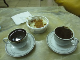 two cups and saucers filled with dark liquid. Plastic dish filled with cinnamon coated light liquid