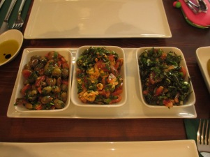 three dishes on a larger white plate with salads