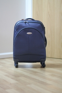 small blue suitcase with four wheels