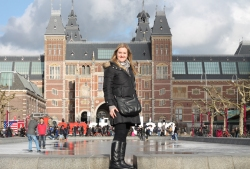 Clare Farrell in coat and black boots in front of Rijksmuseum