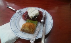 white plate, white paper napkins, cutlery and 3 baklava