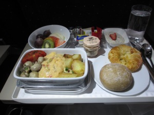 airline breakfast tray with fresh fruit, hot dish, burcher muesli, croissant and breadroll