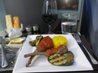 white plate of lamb cutlets, grilled vegetables and rice. Etihad business class