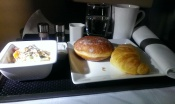 Etihad business class breakfast on tray with yoghurt, croissant and donut, mug of coffee