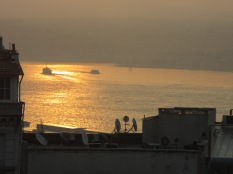 Sunrise on the bosphorus with two boats on the water and view of Asia