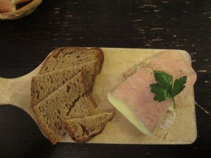 wooden paddle of foie gras with sprig of parsley and slices of bread