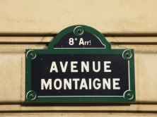 Paris street sign of Ave Montaigne blue sign with white writing on a wall