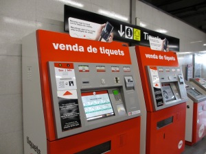 red ticket machine with screens in Spanish