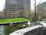 green grass verge with pond and fountain in front