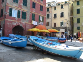 blue fishing boats with pink building and yellow and orange umbrells in the background