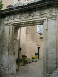 archway with buildings in the background Arles