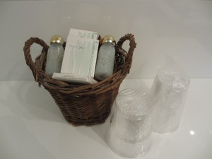brown woven basket with handles, bottles of shampoo and plastic drinking cups