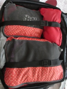 orange and black packing cubes in a suitcase
