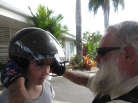 bearded man putting black motorcycle helmet with visor on young girl
