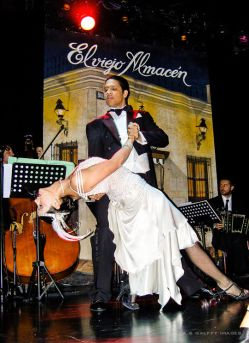 man in tuxedo and woman in white silk dress dancing the tango in Buenos Aires