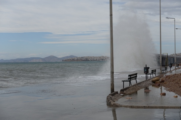 waves crashing against a breakwater with two benches