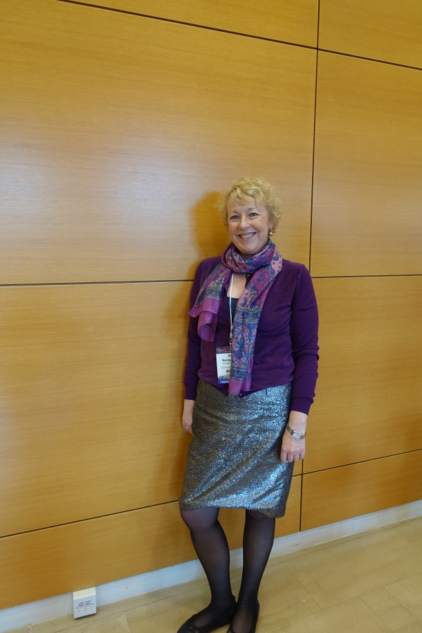 woman wearing silver skirt and purple cardigan