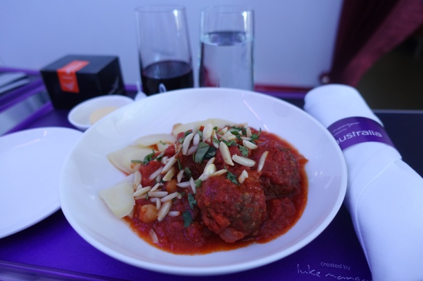 plate of lamb meatballs with tomato sauce on a white plate, served on a tray on Virgin Australia business class
