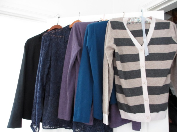 row of jackets, cardigans and blouses on hangers