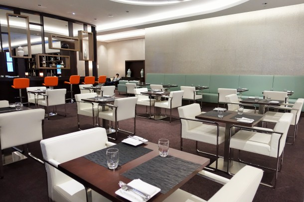 white chairs and dark square tables in the Etihad lounge in Abu Dhabi