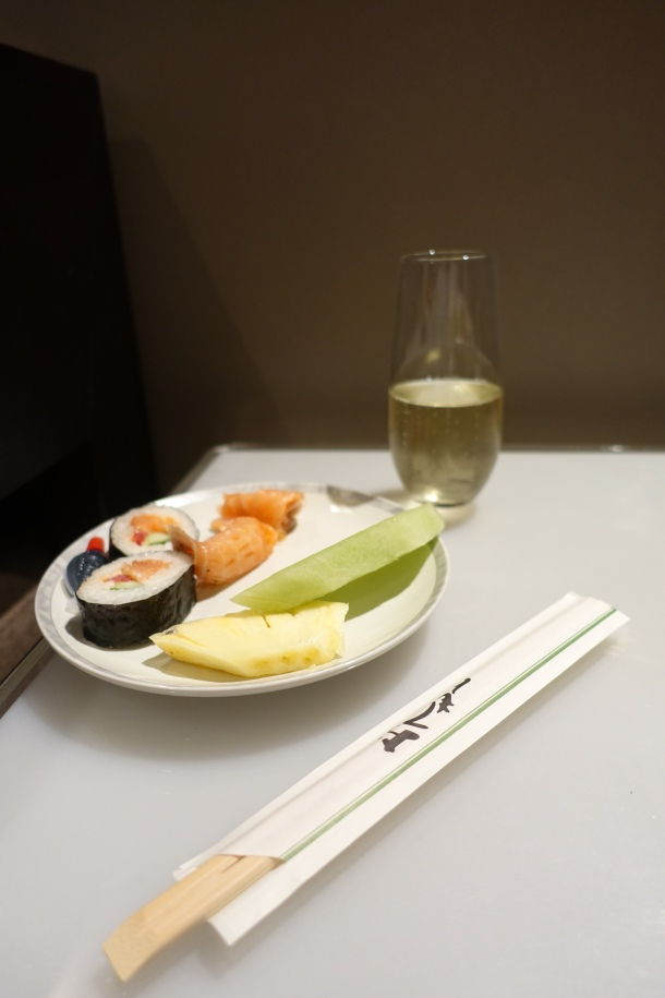 Plate of sushi and fruit, with a glass of Arras champagne in the Singapore Airlines Lounge in Perth
