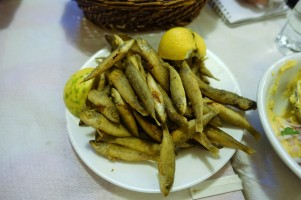 Plate of small whole bait fish with lemon wedges