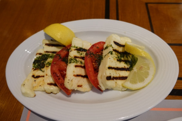 plate of grilled haloumi cheese with tomato slices and lemon wedges