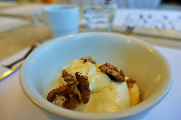Bowl of Greek yoghurt with honey and walnuts scattered on top